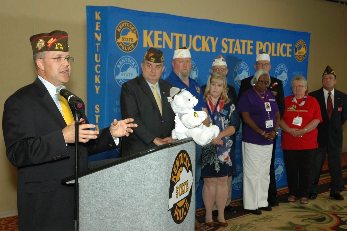 State Surgeon Richard Quire explaining how the Kentucky Department was able to donate $8,000 to the Kentucky State Police's Trooper Teddy Program by requesting VFW Community Service Grants.
